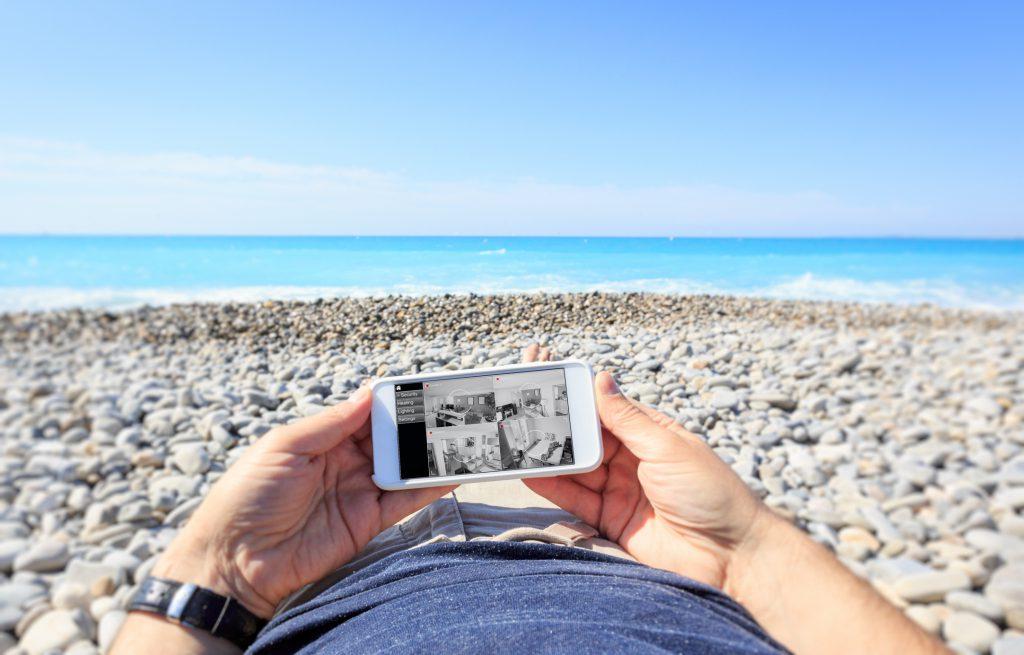 Tourist at the beach checking surveillance cameras at home